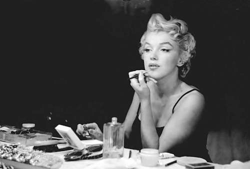 Marilyn-Monroe-putting-on-her-makeup-with-makeup-and-perfume-in-front-of-her-
